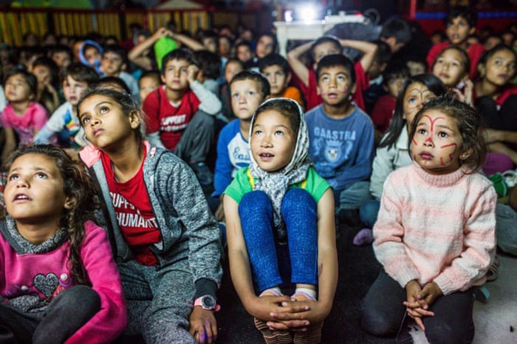 Unger i flyktningeleir som ser på film